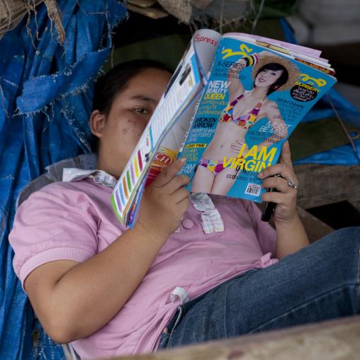 Girl reading a teenage magazine, Thakhek, Laos