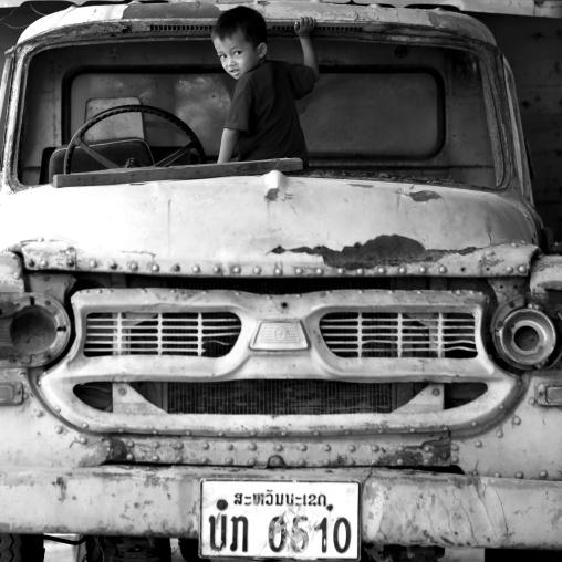 Boy playing in an old car, Thakhek, Laos