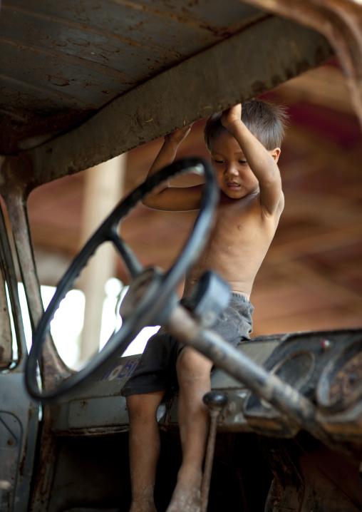 Kid playing in an old car, Thakhek, Laos
