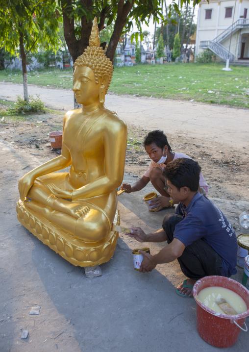 Men painting a buddha statue, Savannakhet, Laos