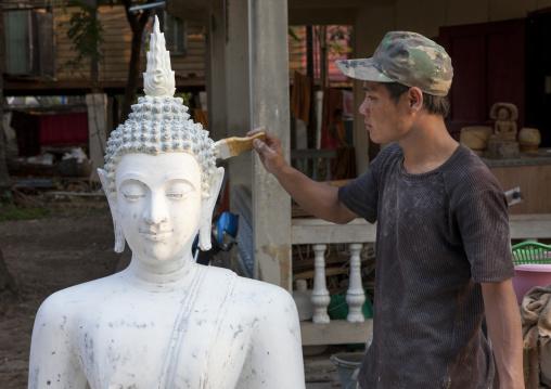 Man painting a buddha statue, Savannakhet, Laos