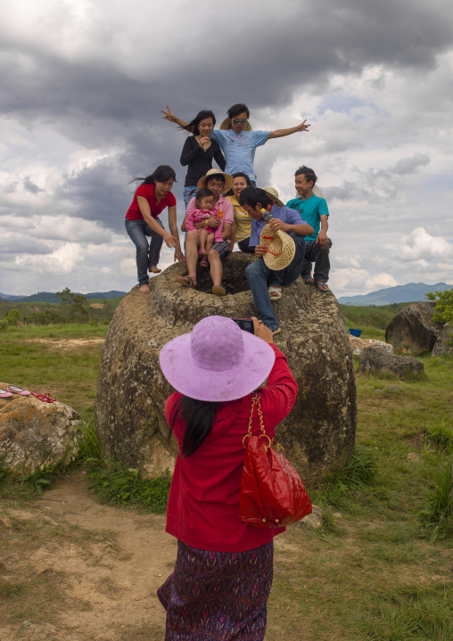 Tourists pausing on a jar, Plain of jars, Phonsavan, Laos
