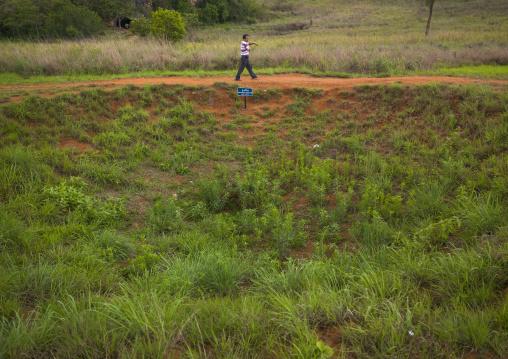 Man passing in front of a bomb crater at plain of jars, Phonsavan, Laos