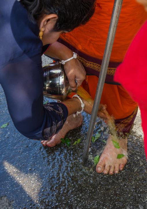 Woman Putting Fresh Water On The Feet Of An Hindu Devotee In Annual Thaipusam Religious Festival In Batu Caves, Southeast Asia, Kuala Lumpur, Malaysia
