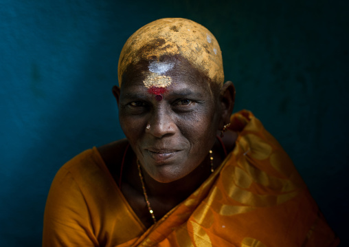 Portrait Of A Woman With Shaved Head Covered With Sandalwood Paste In Batu Caves During Annual Thaipusam Festival, Southeast Asia, Kuala Lumpur, Malaysia