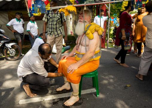Man Putting Fresh Water On The Feet Of An Hindu Devotee In Annual Thaipusam Religious Festival In Batu Caves, Southeast Asia, Kuala Lumpur, Malaysia