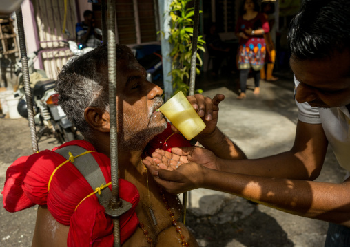 Woman Giving Water To An Hindu Devotee In Annual Thaipusam Religious Festival In Batu Caves, Southeast Asia, Kuala Lumpur, Malaysia