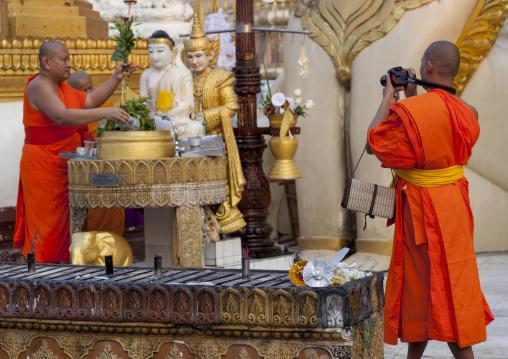 Monks Putting Water On A Statue In Shwedagon Pagoda, Yangon, Myanmar