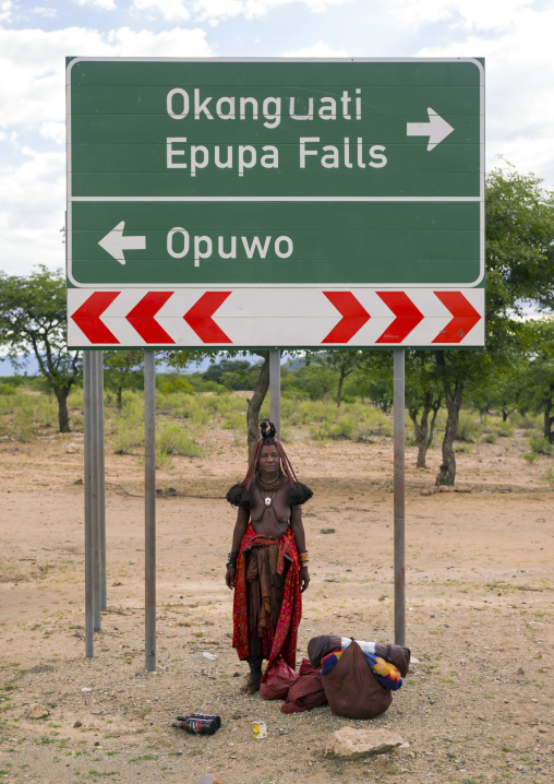 Himba Woman Standing Under A Road Sign, Epupa, Namibia