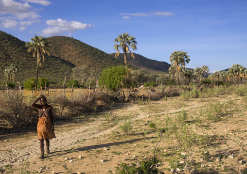 Himba Woman In Front Of Palms Trees In An Arid Landscape, Epupa, Namibia