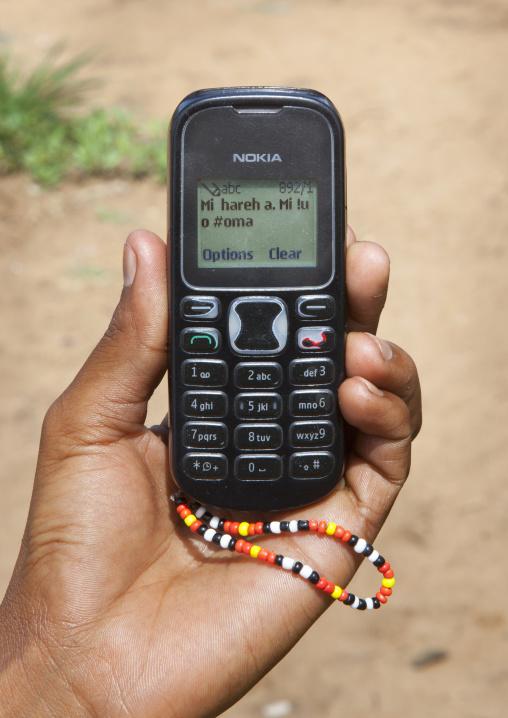 Bushman Showing A Text Message  In San Language On His Mobile Phone, Tsumkwe, Namibia