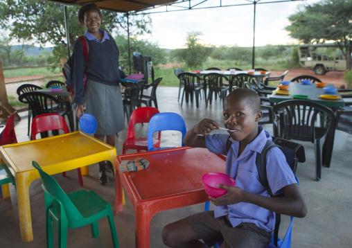 Child Eating At The Africat Foundation Canteen, Okonjima, Namibia