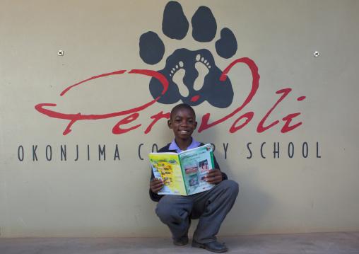 Boy Reading A Book At Africat Foundation, Okonjima, Namibia