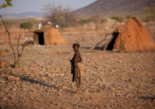 Himba Girl In Front Of Two Huts, Okapale Area, Namibia