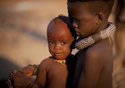 Himba Girl Taking Care Of Her Little Brother Sister