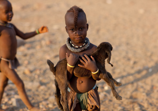 Himba Young Girl Holding A Lamb In Her Arms, Okapale Area, Namibia