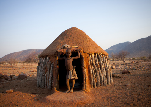 Himba Boy In The Entrance Of His Hut, Okapale Area, Namibia