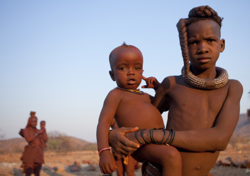 Himba Girl Taking Care Of Her Little Brother Sister, Okapale Area, Namibia