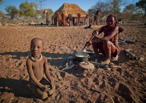 Himba Boy With His Mother Preparing The Meal, Village Of Karihona, Namibia