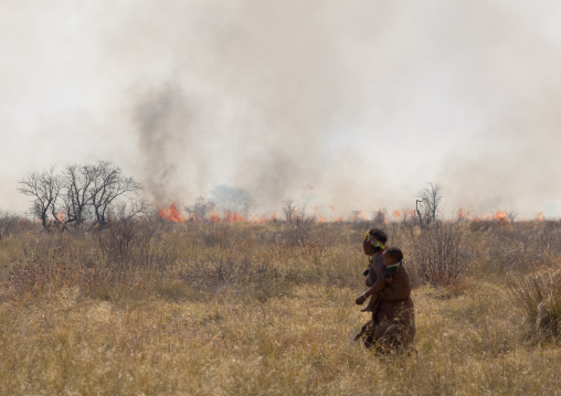 San Woman With Her Baby Passing By A Fire In The Bush, Namibia