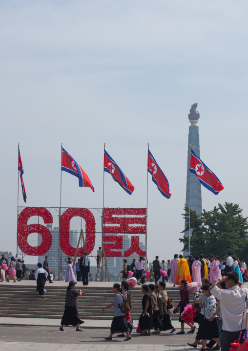 North Korean people with plastic bunches of red flowers celebrating the 60th anniversary of the regim, Pyongan Province, Pyongyang, North Korea