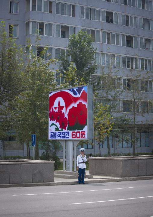 North Korean male traffic security officer in the street under a propaganda billboard, Pyongan Province, Pyongyang, North Korea