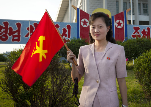 North Korean woman with a workers' Party of North Korea flag during the september 9 parade, Pyongan Province, Pyongyang, North Korea