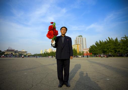 North Korean man with plastic flowers during the september 9 parade, Pyongan Province, Pyongyang, North Korea