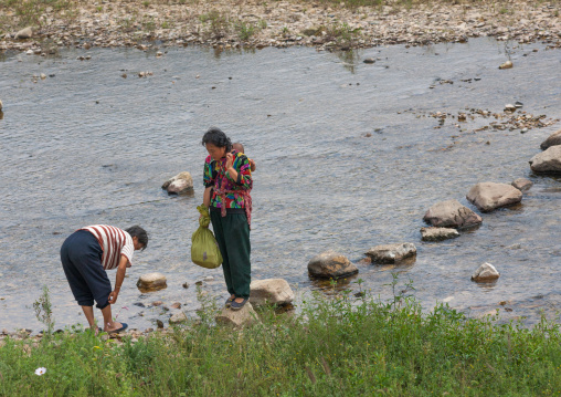 North Korean women walking on stones to cross a river, North Hwanghae Province, Sariwon, North Korea