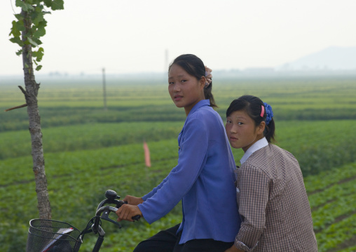 North Korean girls on their bicycles in the countryside, Kangwon Province, Chonsam Cooperative Farm, North Korea