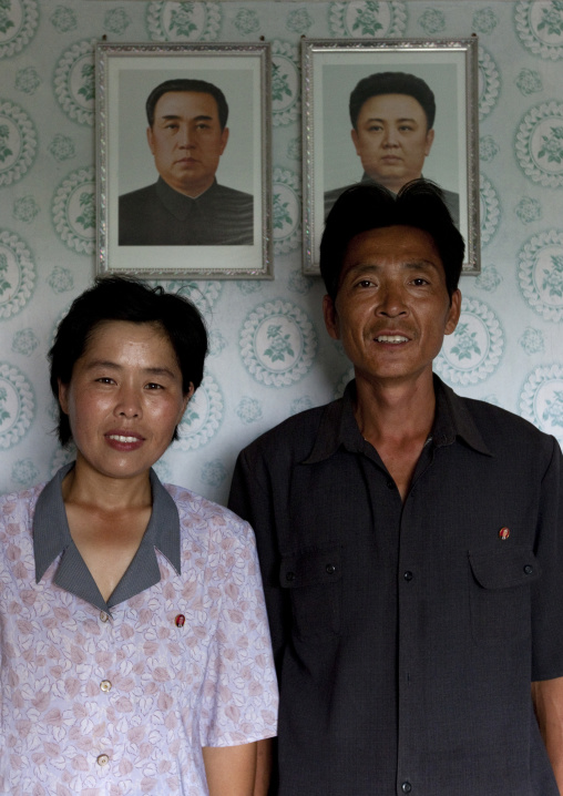 Smiling North Korean couple in front of the official portraits of the Dear Leaders in their house, Kangwon Province, Chonsam Cooperative Farm, North Korea