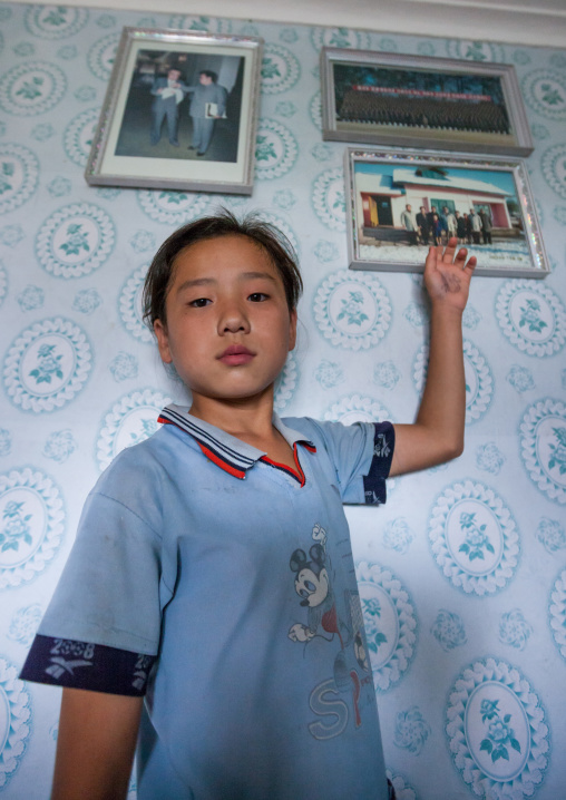 North Korean girl posing below the portraits of the Dear Leaders inside her home, Kangwon Province, Chonsam Cooperative Farm, North Korea