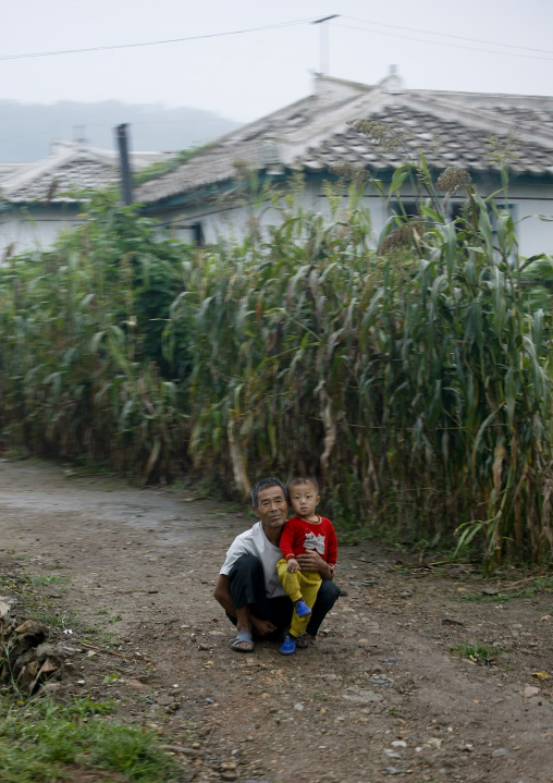 North Korean man with his son in the countryside, North Hwanghae Province, Sariwon, North Korea