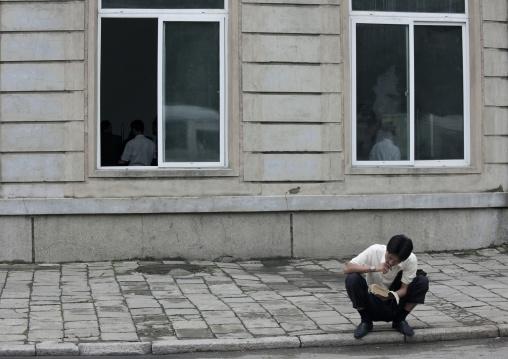 North Korean man reading a book in the street, Pyongan Province, Pyongyang, North Korea