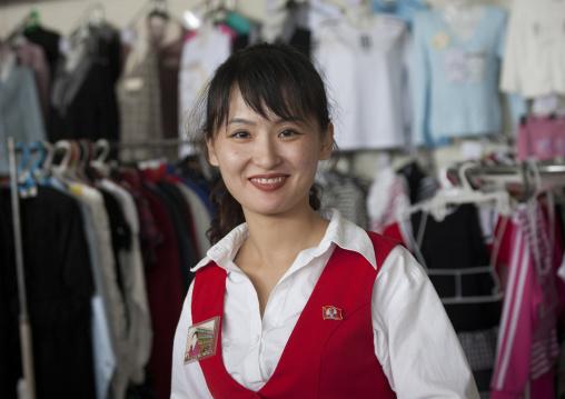 Smiling North Korean woman selling clothes in a shop, Pyongan Province, Pyongyang, North Korea