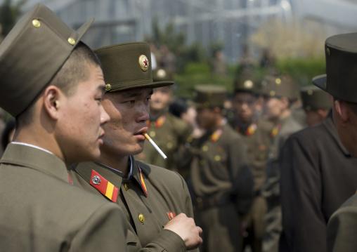 North Korean soldeirs smoking cigarettes in the street, Pyongan Province, Pyongyang, North Korea