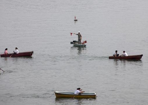 Man monitoring North Korean people in rowing boats on Taedong river, Pyongan Province, Pyongyang, North Korea