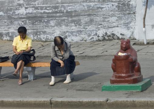 North Korean women sit on a bench near a trash bin, Pyongan Province, Pyongyang, North Korea