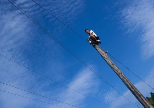 North Korean man working on telephone line pole, North Hamgyong Province, Chilbo Sea, North Korea