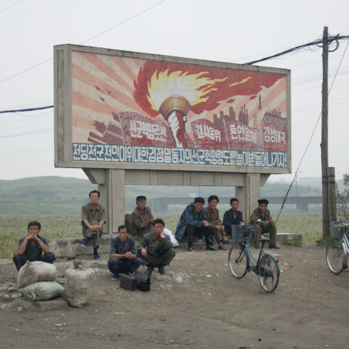 North Korean workers having a rest below a juch tower flame billboard, South Hamgyong Province, Hamhung, North Korea
