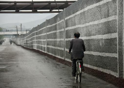 North Korean man riding a bicycle alongside a wall, South Hamgyong Province, Hamhung, North Korea