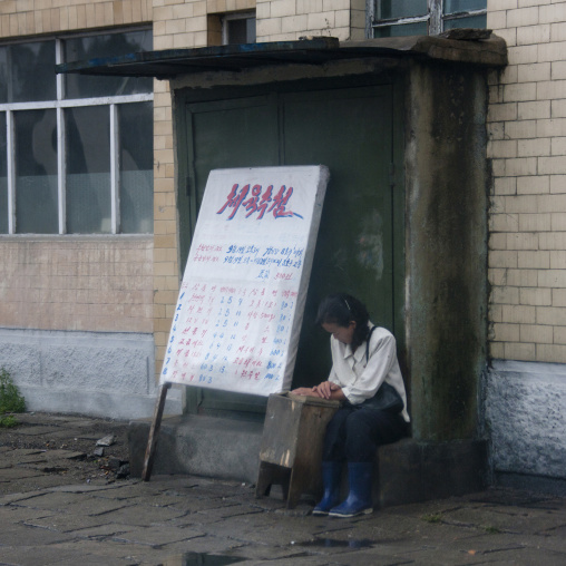 North Korean woman in the street with lottery board, South Hamgyong Province, Hamhung, North Korea