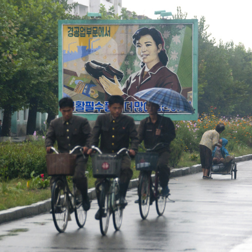North Korean soldiers riding bicycles on a wet road with an advertising poster for shoes in background, South Hamgyong Province, Hamhung, North Korea