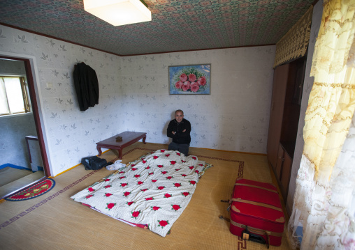 Tourist in a North Korean bedroom in a homestay, North Hamgyong Province, Jung Pyong Ri, North Korea