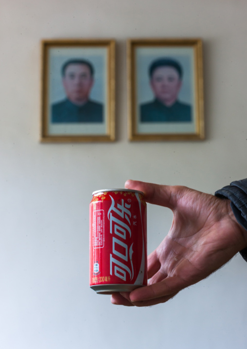 Can of North Korean coca cola in front of the portraits of Kim il Jong and Kim Jong il, Ryanggang Province, Samjiyon, North Korea