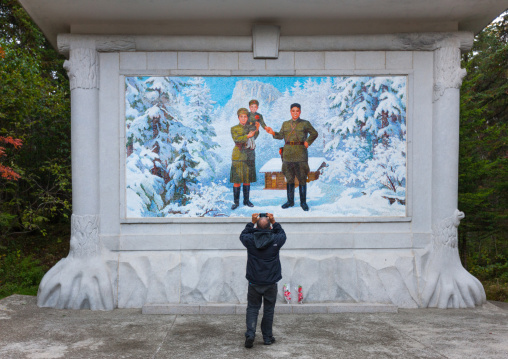 Foreign tourist taking a picture of a propaganda fresco depicting Kim il song as a child with his parents, Ryanggang Province, Samjiyon, North Korea