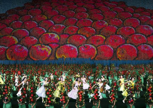 Women dancing in front of apples made by children pixels holding up colored boards during Arirang mass games in may day stadium, Pyongan Province, Pyongyang, North Korea