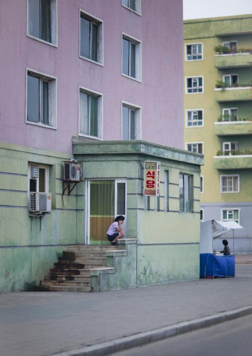 North Korean woman using mobile phone in the street, Pyongan Province, Pyongyang, North Korea