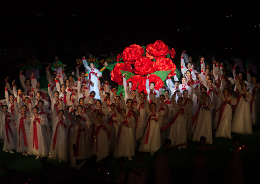 North Korean women dancing in front of a giant Kimilsungia flower during the Arirang mass games in may day stadium, Pyongan Province, Pyongyang, North Korea