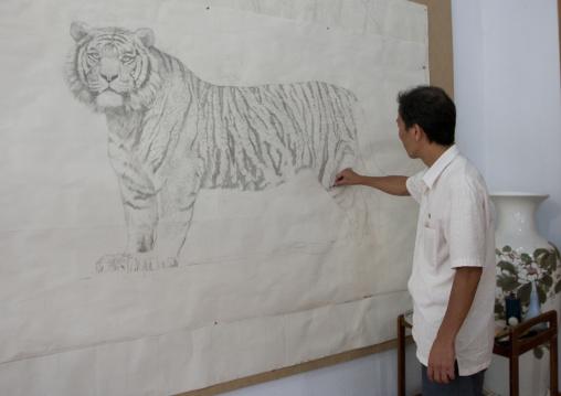 North Korean artist drawing a tiger at Mansudae art studio, Pyongan Province, Pyongyang, North Korea